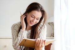 Estudante fêmea com o livro de leitura da pena Fotografia de Stock