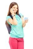 Estudante fêmea com um saco que fala em um telefone e que guarda um credi Imagens de Stock