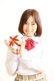 Estudante fêmea da High School que oferece um presente Fotografia de Stock