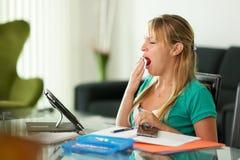 Estudante fêmea da jovem mulher que boceja ao estudar imagens de stock royalty free