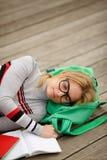 Estudante fêmea de sono com o livro no assoalho de madeira Imagens de Stock