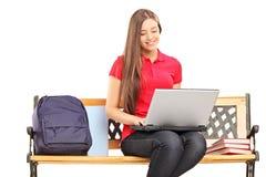 Estudante fêmea de sorriso que senta-se em um banco de madeira e que trabalha sobre Fotos de Stock Royalty Free
