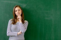 Estudante fêmea de sorriso seguro novo da High School que está na frente do quadro na sala de aula imagem de stock