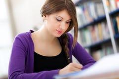 Estudante fêmea em uma biblioteca imagens de stock royalty free