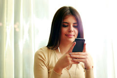 Estudante fêmea feliz novo que usa o smartphone fotos de stock