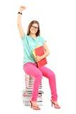 Estudante fêmea feliz que senta-se em uma pilha de livros imagens de stock royalty free
