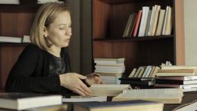 Estudante fêmea focalizado que trabalha com livros em uma biblioteca no University College Estudante cansado que prepara-se para  vídeos de arquivo
