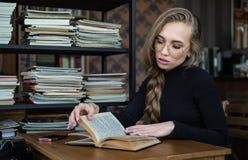 Estudante fêmea na biblioteca, está sentando-se na mesa e no conceito da melhoria do estudo, da educação e do auto foto de stock royalty free