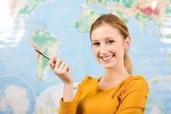 Estudante fêmea na frente do mapa de mundo Fotografia de Stock Royalty Free