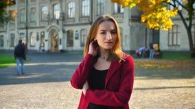 Estudante fêmea novo com as mãos cruzadas que olham seguramente em uma câmera no fundo da universidade video estoque