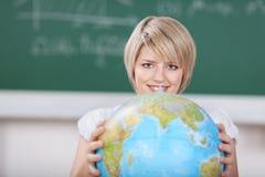 Estudante fêmea novo com um globo do mundo Imagens de Stock