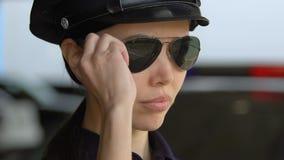 Estudante fêmea novo da academia de polícia no tampão que põe sobre óculos de sol, primeiro dever video estoque