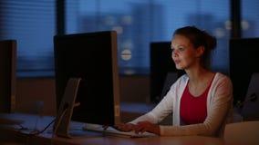 Estudante fêmea novo em uma sala de aula do computador