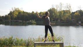 Estudante fêmea novo feliz atrativo que aprecia um dia livre no parque que dança próximo a um lago e que lança seu cabelo vídeos de arquivo
