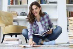 Estudante fêmea novo que estuda em casa, sentando-se no assoalho contra o interior doméstico acolhedor, cercado com a pilha dos l fotografia de stock
