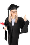 Estudante fêmea novo que guarda um diploma e que dá o polegar acima Fotografia de Stock