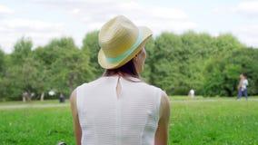 Estudante fêmea novo que senta-se na grama no terreno da faculdade que relaxa Turista que sonha acordado em público o parque filme