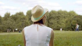 Estudante fêmea novo que senta-se na grama no terreno da faculdade que relaxa Turista que sonha acordado em público o parque vídeos de arquivo