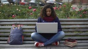 Estudante fêmea novo que senta-se no banco completo-absorvido fora no estudo video estoque