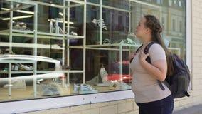 Estudante fêmea obeso triste que olha sapatas elegantes no boutique, inseguranças vídeos de arquivo
