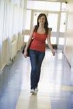 Estudante fêmea que anda abaixo do corredor da universidade Imagens de Stock Royalty Free