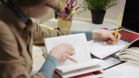 Estudante fêmea que estuda em casa usando um livro de estudo filme