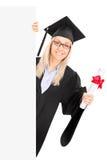 Estudante fêmea que guarda um diploma e que levanta atrás do painel vazio Fotografia de Stock