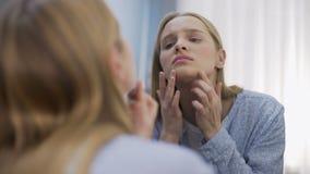 Estudante fêmea que olha tristemente na reflexão da cara em dificuldades novas da idade do espelho filme