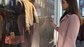 Estudante fêmea que olha tristemente a roupa cara no boutique, compra da janela filme