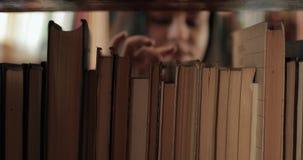 Estudante fêmea que seleciona o livro na biblioteca filme