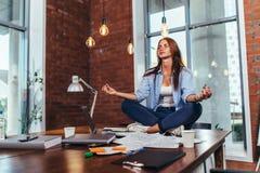 Estudante fêmea que senta-se na pose dos lótus na tabela em sua sala que medita o relaxamento após o estudo e a preparação para o fotografia de stock