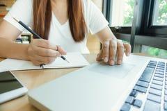 Estudante fêmea que toma notas de um livro na biblioteca Mulher asiática nova que senta-se na tabela que faz atribuições na bibli Fotos de Stock