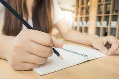 Estudante fêmea que toma notas de um livro na biblioteca Mulher asiática nova que senta-se na tabela que faz atribuições na bibli Fotografia de Stock