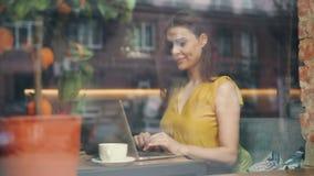 Estudante fêmea que usa o laptop no café que sorri tocando no teclado vídeos de arquivo