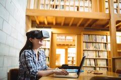 Estudante fêmea que usa o portátil e os auriculares da realidade virtual na biblioteca Fotos de Stock