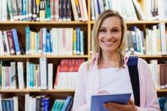 Estudante fêmea que usa a tabuleta na biblioteca imagem de stock