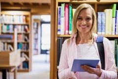 Estudante fêmea que usa a tabuleta na biblioteca foto de stock