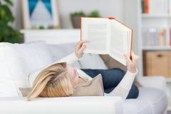 Estudante fêmea Reading Book While que encontra-se no sofá Fotografia de Stock Royalty Free