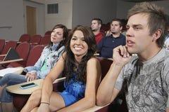 Estudante fêmea Sitting With Classmates fotografia de stock royalty free