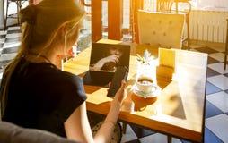 Estudante fêmea talentoso no café usando dispositivos modernos fotos de stock