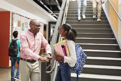 Estudante fêmea Talking With Teacher da High School no corredor ocupado imagem de stock royalty free