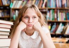 Estudante fêmea triste na biblioteca Fotografia de Stock Royalty Free