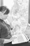 Estudante feliz bonito com um portátil que senta-se contra a janela Imagem de Stock