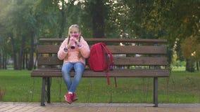 Estudante feliz com chá bebendo da mochila do copo da garrafa térmica como o assento no banco vídeos de arquivo