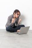 Estudante feliz com punhos acima para a convicção no assoalho do escritório imagem de stock