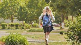 A estudante feliz de onze-ano corre com uma trouxa após a escola filme
