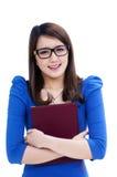 Estudante feliz nos eyeglasses que abraçam seu livro fotos de stock royalty free
