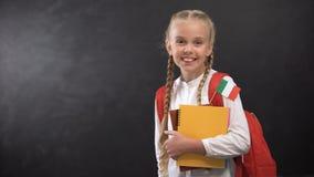 Estudante feliz que guarda livros com a bandeira de Itália, pronta para aprender a língua estrangeira filme