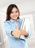 Estudante feliz que mantém alguns livros e polegares Foto de Stock Royalty Free