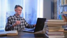 Estudante feliz que trabalha no portátil na biblioteca filme